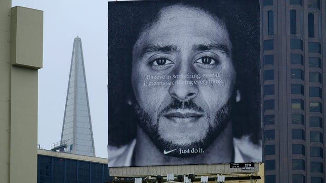 A large billboard stands on top of a Nike store showing former San Francisco 49ers quarterback Colin Kaepernick at Union Square, Wednesday, Sept. 5, 2018, in San Francisco. An endorsement deal between Nike and Colin Kaepernick prompted a flood of debate Tuesday as sports fans reacted to the apparel giant backing an athlete known mainly for starting a wave of protests among NFL players of police brutality, racial inequality and other social issues. (AP Photo/Eric Risberg)