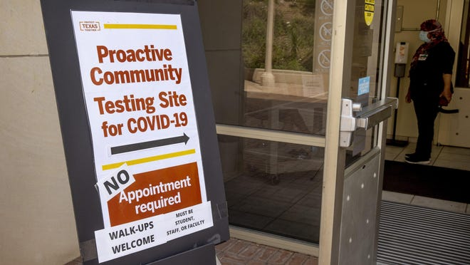 A sign directs people to a COVID-19 testing site at the Student Services Building on the University of Texas campus Monday.