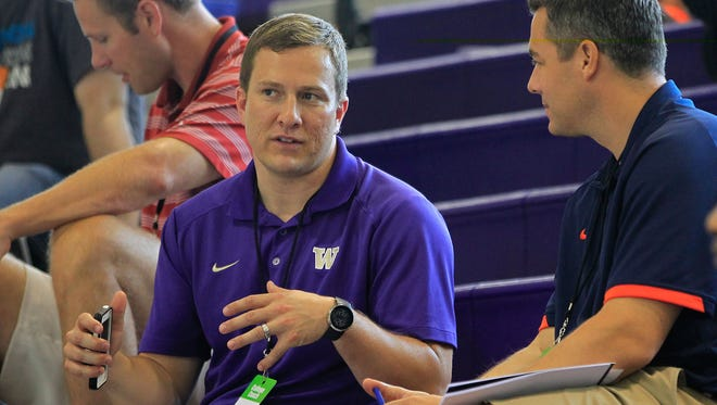 Then-Washington Huskies assistant basketball coach T.J. Otzelberger ( l ) talks with Virginia Cavaliers basketball coach Tony Bennett ( r ) in the stands during the game between Team France and Team USA East during the Nike Global Challenge in 2013.