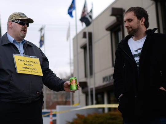 Bronson Smith (center) and Brandon Falish, both Green Bay residents, discuss about police behavior with two more protesters (not pictured) in front of the Green Bay police station on Adams Street in protest.