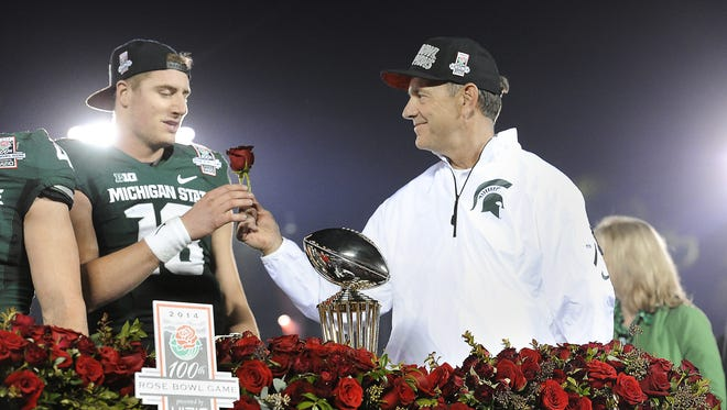 MSU coach Mark Dantonio hands a rose to quarterback Connor Cook after the Spartan's 24-20 victory over Stanford in the Rose Bowl. MSU appears headed back to a major bowl - its chances at the playoff are even existent, however slim.