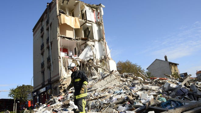 A firefighter searches through the rubble of a four-story residential building that collapsed following a blast in Rosny-sous-Bois in the eastern suburbs of Paris on Aug. 31, 2014.