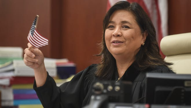 """Frances Tydingco-Gatewood, chief judge, waves a U.S. flag at a """"Let Freedom Ring"""" Naturalization Ceremony at the District Court of Guam on Jan. 20."""