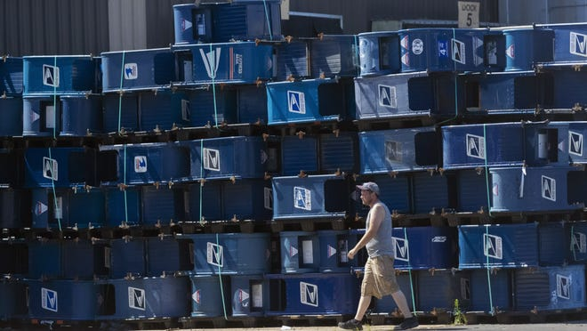 A worker walks past mailboxes that were removed from service, Thursday, Aug. 20, 2020, at Hartford Finishing in Hartford, Wis. USPS contracts with Hartford Finishing to repair or destroy old mailboxes. The mailboxes shown could have been removed, after a public notice, because of a lack of use, following a long-established process, or they could have been replaced with new boxes because of their condition.