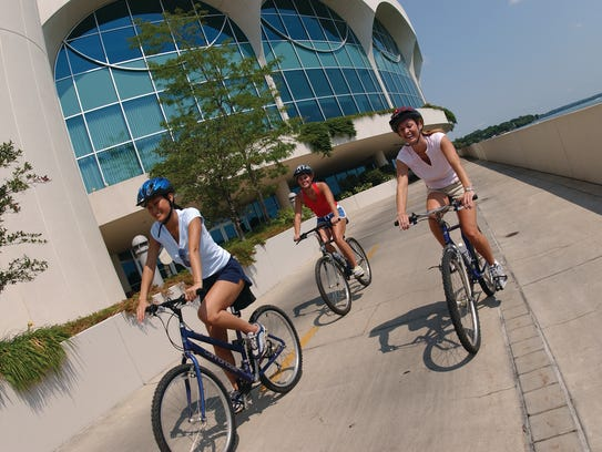 Cyclists ride past Monona Terrace in Madison.