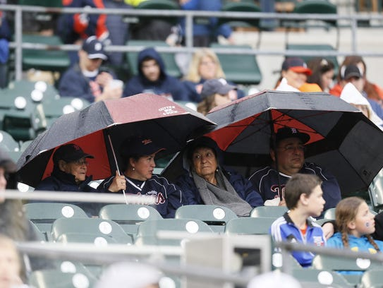 Tigers fans under umbrellas in the rain in the first