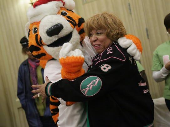 Tigers mascot Paws hugs Tau Alpha Omega chapter president