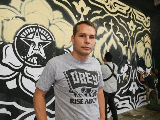 Artist Shepard Fairey works on a mural in The Belt