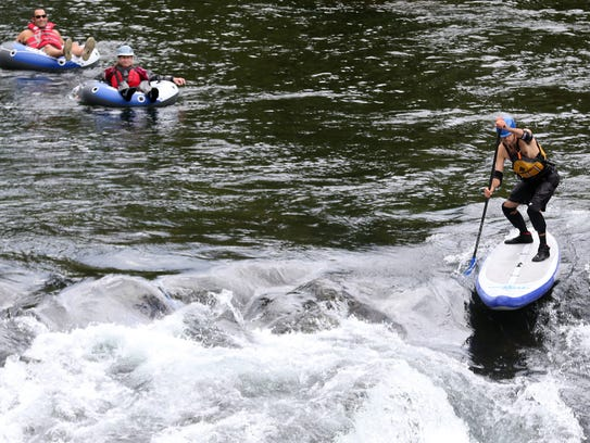 A paddle boarder and rafters prepare to go over the