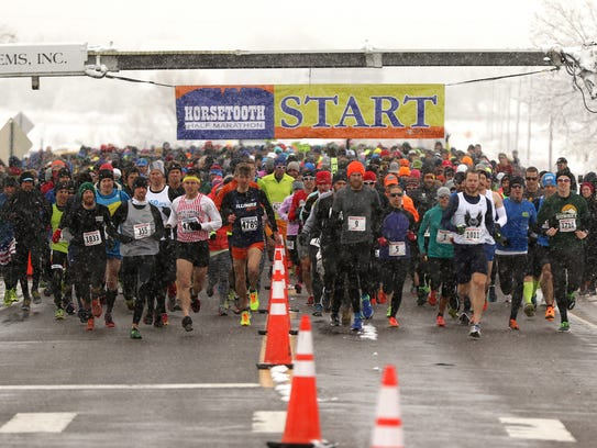 Runners make their way through a windy and snowy Horsetooth