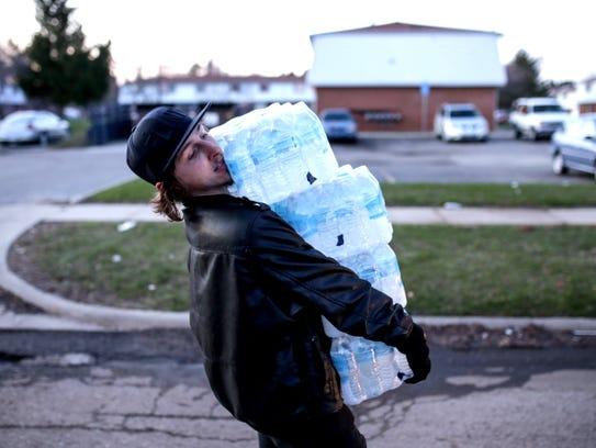 Flint resident Christopher Kabel carries multiple cases