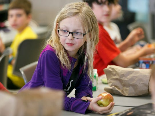 Kennedi Smith eats an apple from a free lunch provided