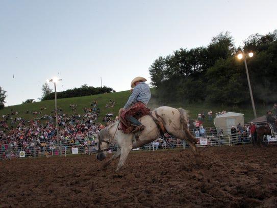 Charlie Isaacs rides a bronco Friday at the Johnson
