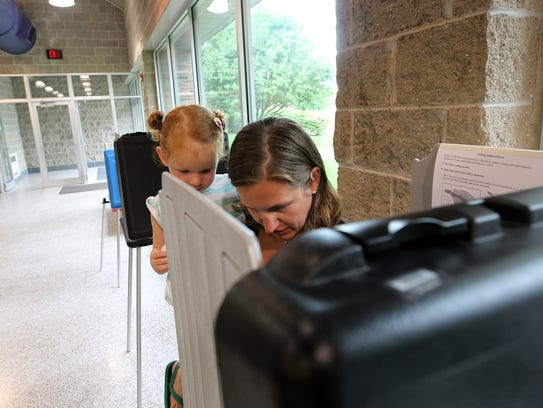 Kristin Wendlandt votes with help from her 3-year-old