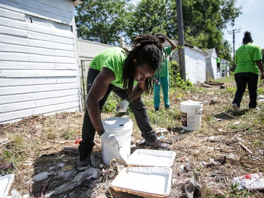 Jaysin Henry Johnson, 17, of Detroit pours paint into