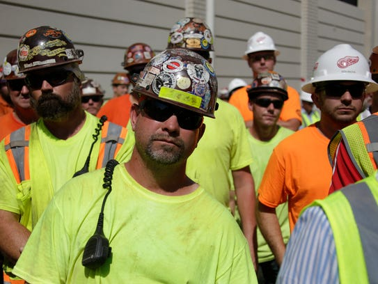 Ironworkers look on as the Ilitches' Olympia Development