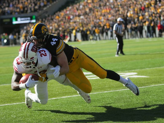 Iowa linebacker Ben Niemann tackles Wisconsin running