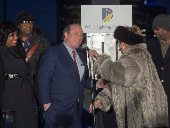 Detroit Mayor Mike Duggan, center, joins others to