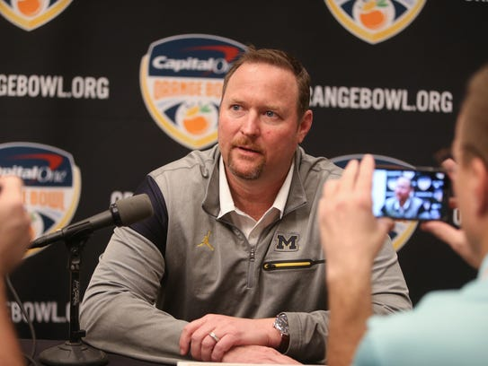 Michigan offensive coordinator Tim Drevno  talks with