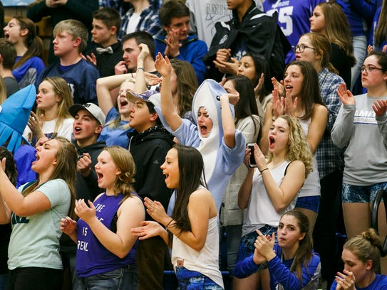 Amity students and fans cheer as they score a basket
