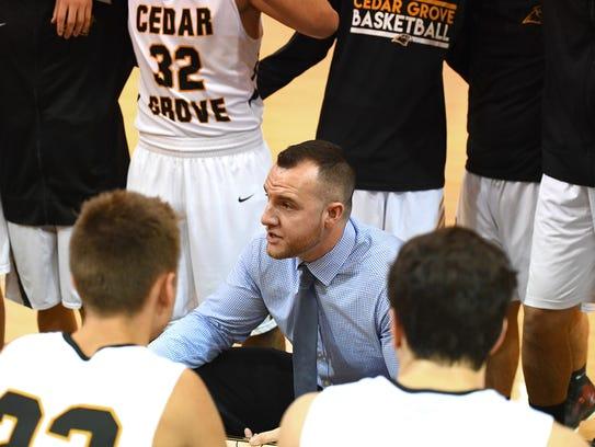 Cedar Grove boys basketball coach TJ Jones talks to his team in a huddle.