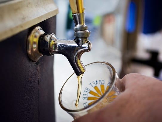 A volunteer pours a Blue Point Toasted Lager for an