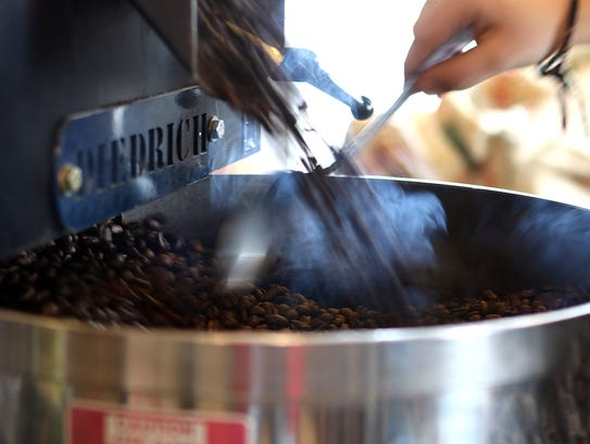 Freshly roasted coffee beans pour out of the roaster