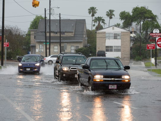 Cars drive thought standing water on Santa Fe Street