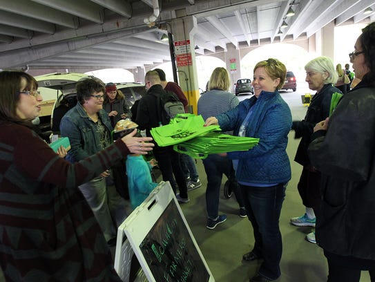 Tammy Neumann hands out shopping bags to customers
