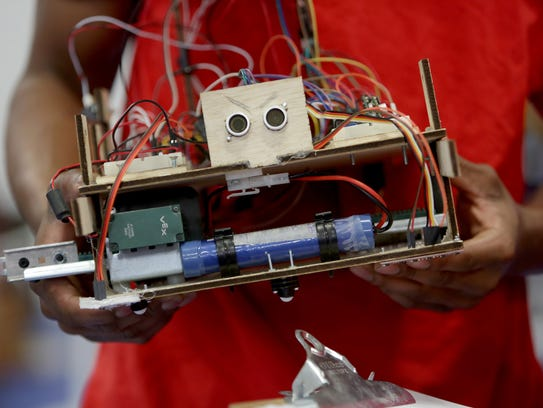 Nathaniel Lee, 18, holds his robot after the competition