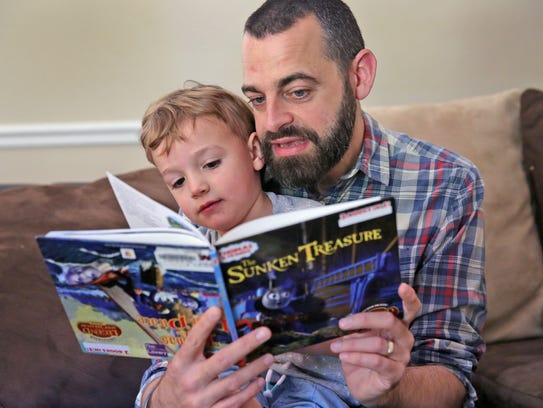 Adam Hayden reads with his son Noah at their Greenwood