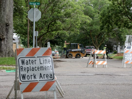 Signs for water line replacement are seen as crews