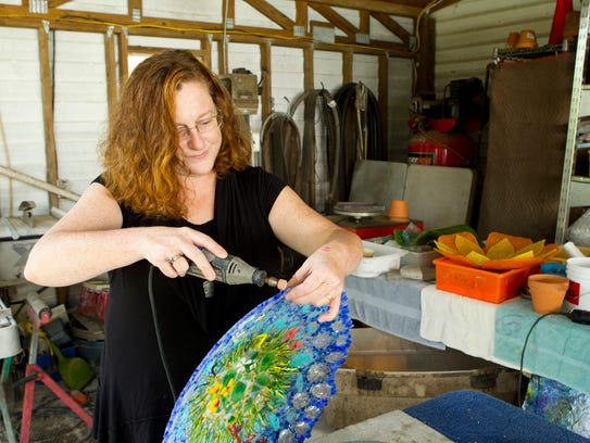 Cheryl Sattler sands down sharp edges on glass artwork