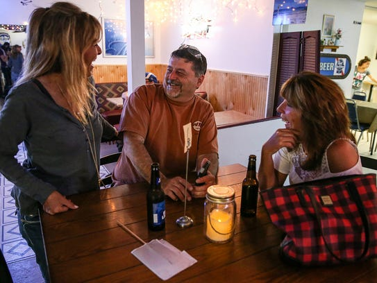 From left, Joan Pohlman chats with two regular customers,