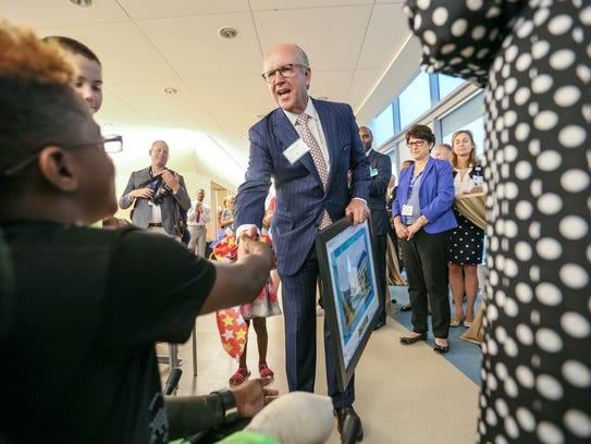 Trevor Fetter, CEO of Tenet healthcare, receives a