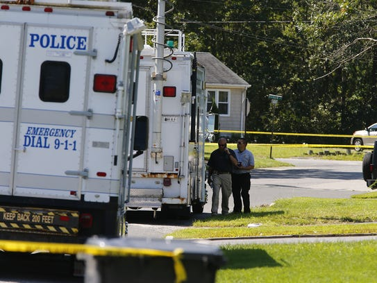 Police officers gather along Meridian Drive in Brick