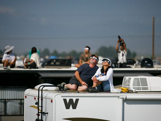 Mike Flynn and Nona Dyck watch the sun as the eclipse
