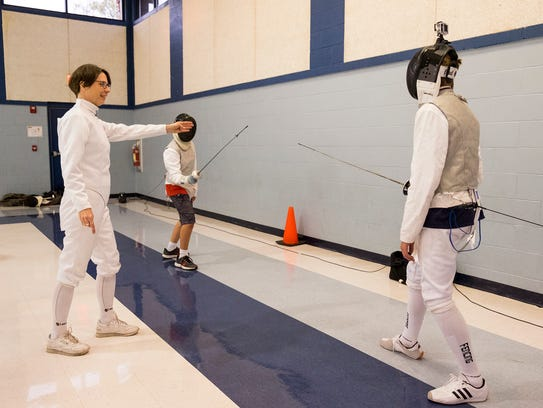 Fencing Instructor Marie Warren, left, calls a bout