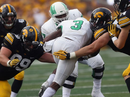 Iowa's Nathan Bazata, left, and Matt Nelson tackle