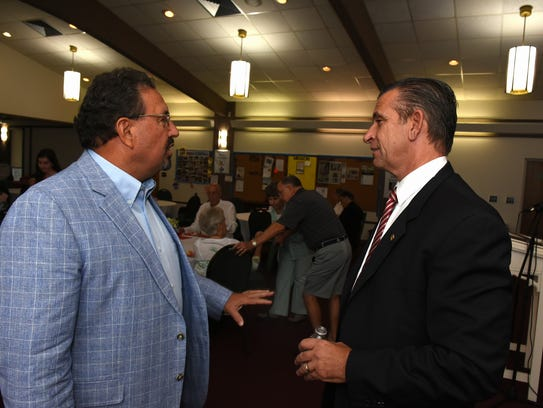 City Councilor Howard Reed, left, talks with State