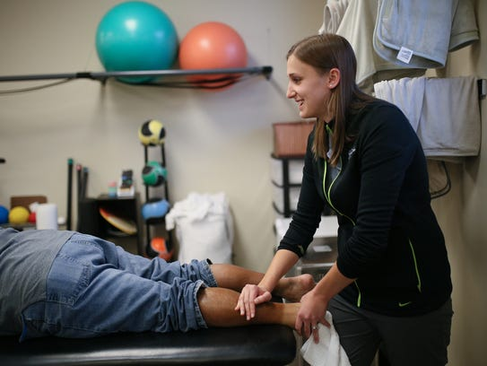 Physical therapist Gina Gee, 26, of Wyandotte massages a client's calf muscle at Team Rehabilitation Physical Therapy in Taylor.