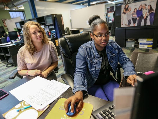 Chloe Stoner, 25, of Clawson, left, works with Candace Mills, 28, of Redford Township, both care coordinators, to process a new referral at Custom Home Health.