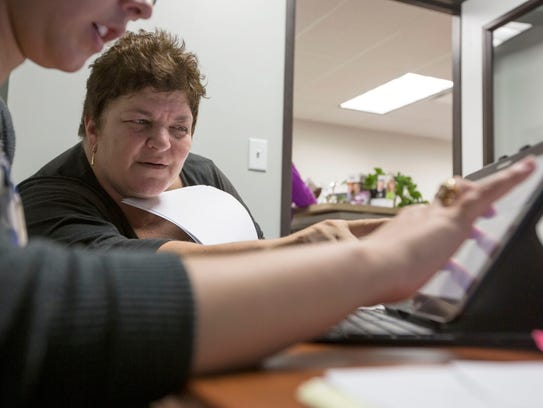 Staffing manager Kylie Montano, left, works out a schedule with caregiver Lisa Carlesso during an open house at Home Instead Senior Care.