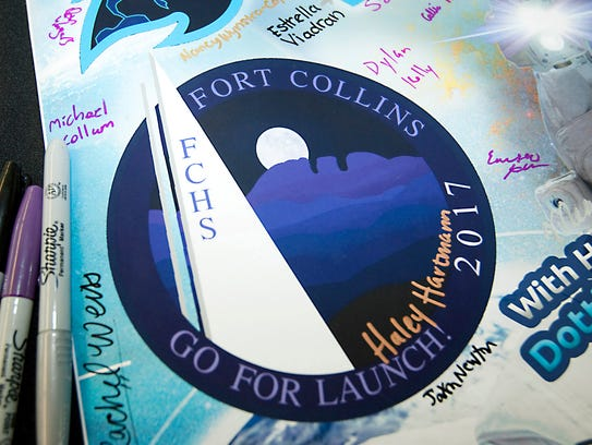 A student-signed poster shows the winning patch designed