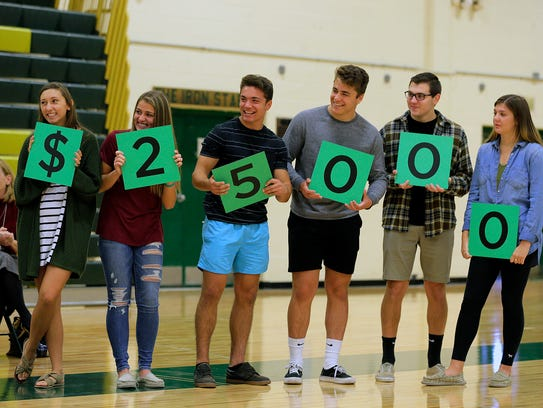 A group of seniors hold up cards which reveal the amount