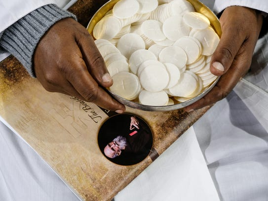 Father Wolfgang Pisa of Tanzania holds a bowl of hosts