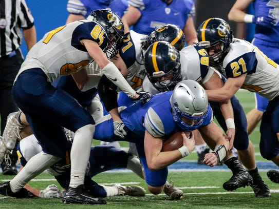 Saginaw Nouvel quarterback Tate Hausbeck (7) is stopped