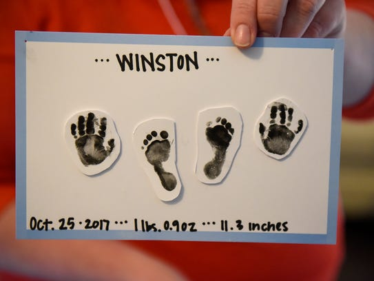 Jenny Borgstrom holds a sign with the handprints and