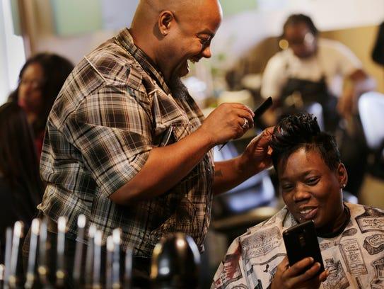 Hair stylist Martin Wheeler shares a laugh with customer