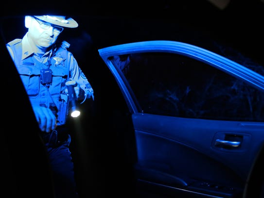Oregon State Police trooper Cristian Cuevas looks for